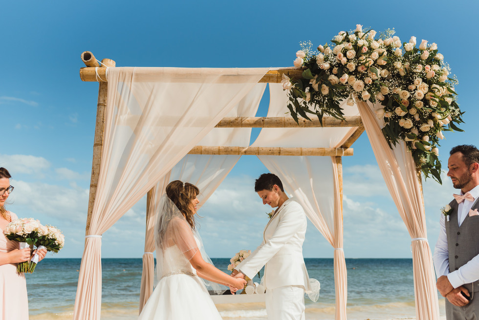 brides holding hands under the wedding alter during beach ceremony at Now Sapphire Resort in Mexico