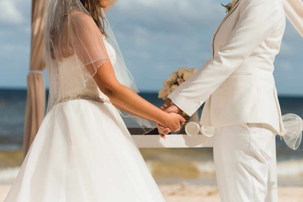 brides holding hands during beach ceremony at Now Sapphire Resort in Mexico