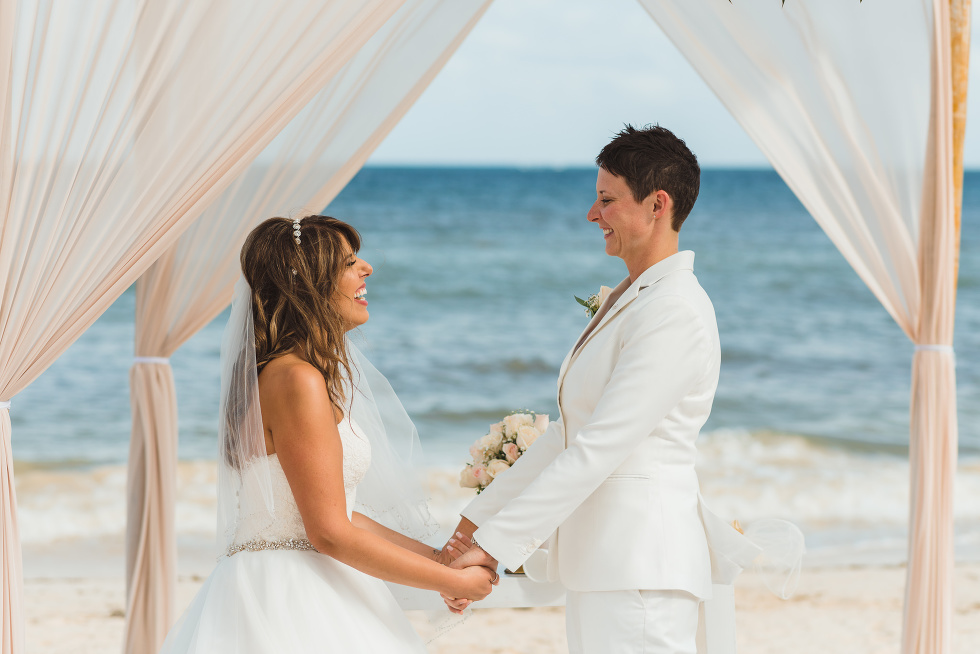 brides holding hands during beach ceremony in front of ocean at Now Sapphire Resort in Mexico