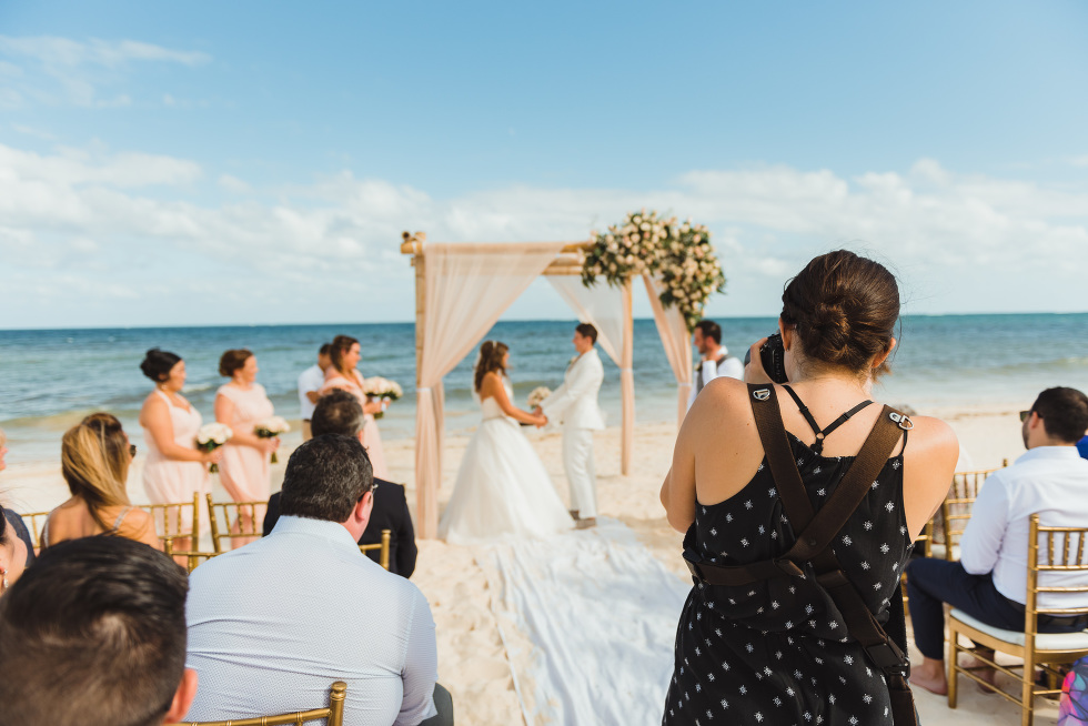 photography taking picture of brides holding hands during beach ceremony in front of ocean at Now Sapphire Resort in Mexico