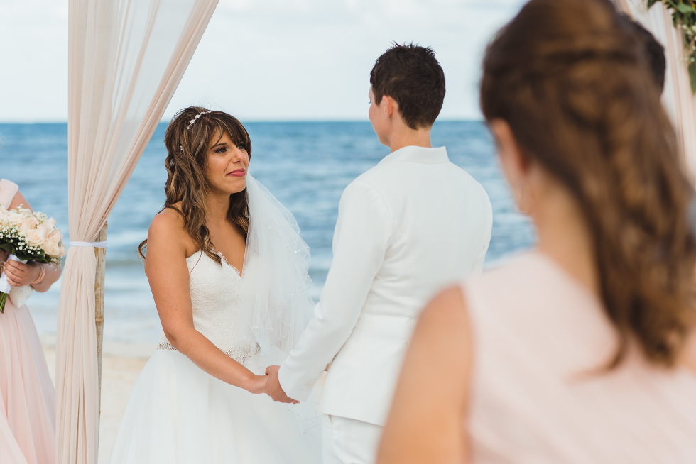 bride tearing up while holding hands during beach ceremony in front of ocean at Now Sapphire Resort in Mexico