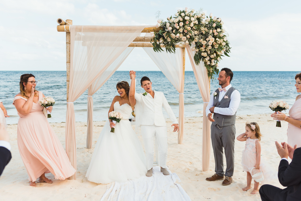 brides lifting hands together after beach ceremony in front of ocean at Now Sapphire Resort in Mexico