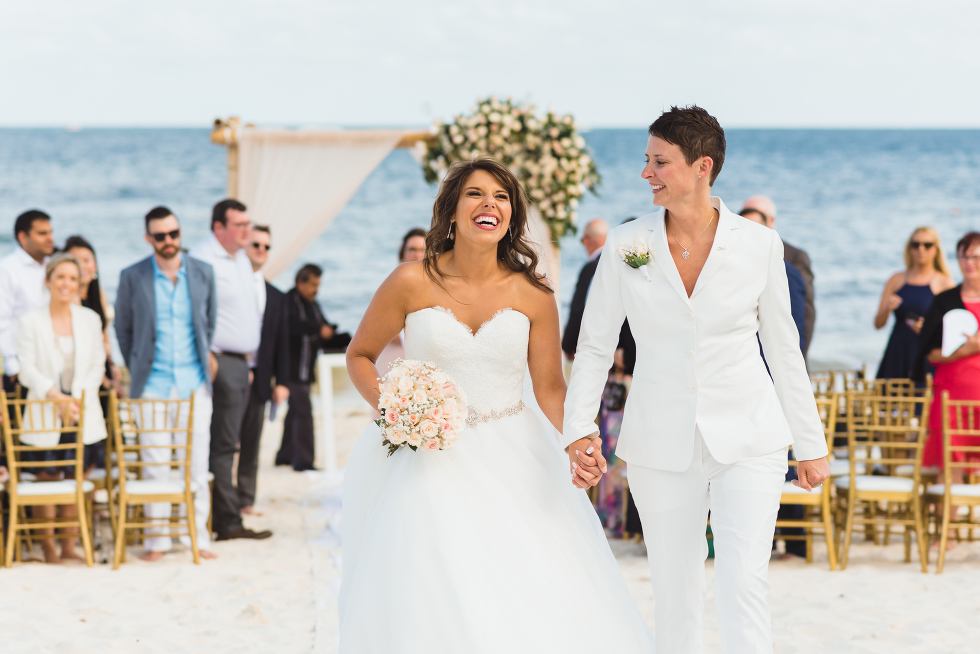 brides smiling and holding hands as they exit beach ceremony in front of ocean at Now Sapphire Resort in Mexico
