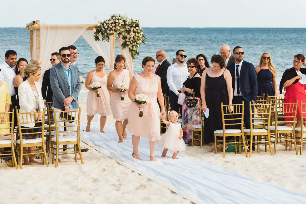 wedding party and guests exit beach ceremony in front of ocean at Now Sapphire Resort in Mexico