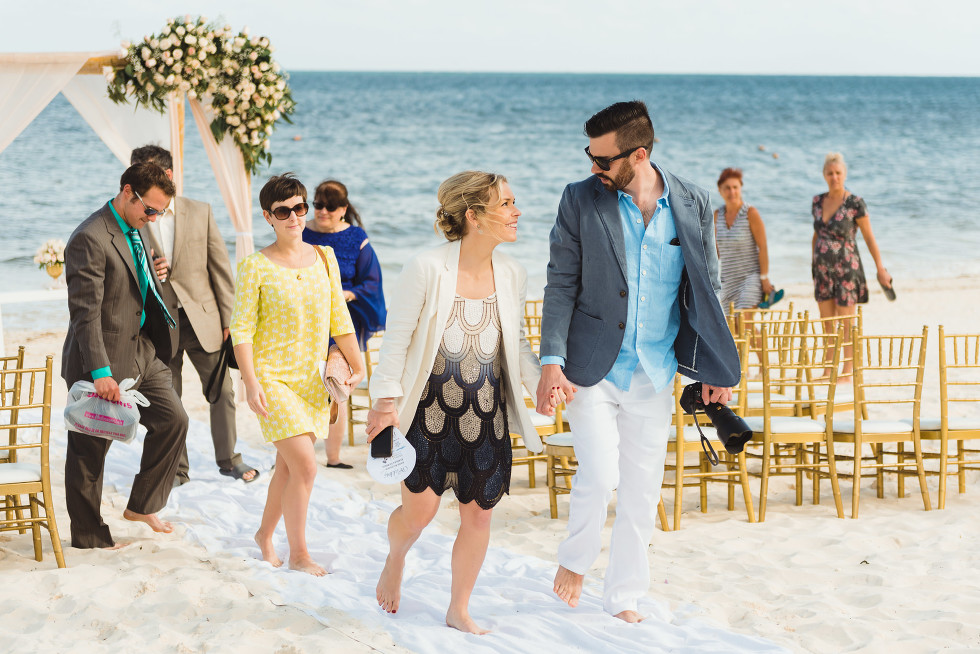 wedding guests exit beach ceremony in front of ocean at Now Sapphire Resort in Mexico