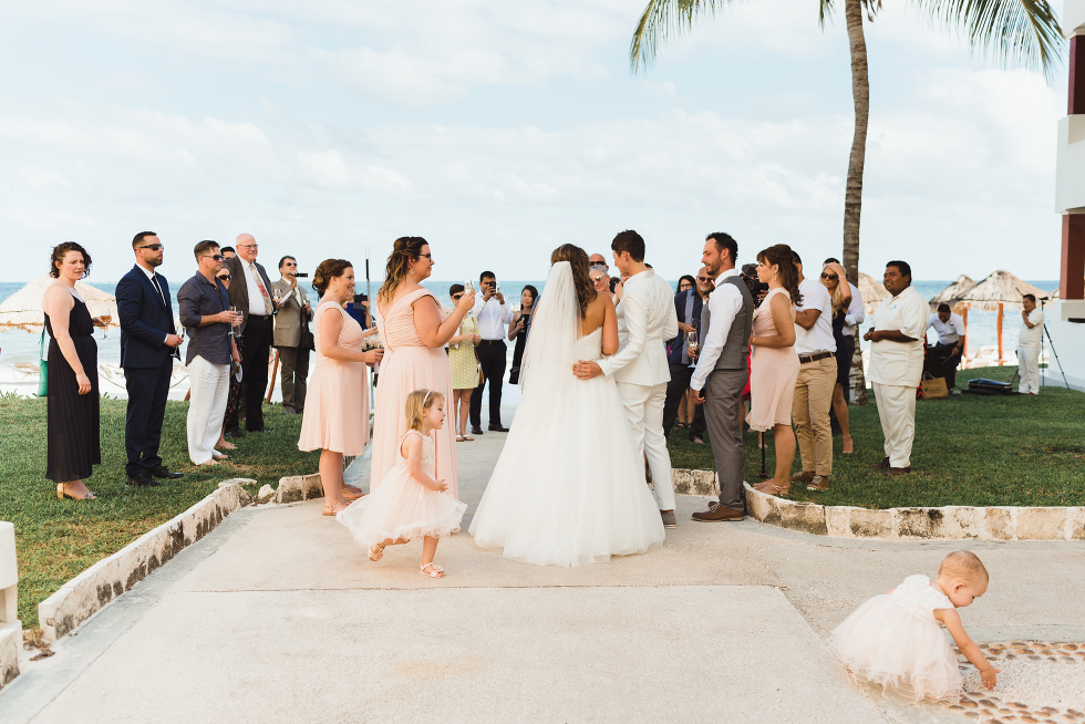 brides holding a toast with wedding guests after wedding ceremony in front of ocean at Now Sapphire Resort in Mexico