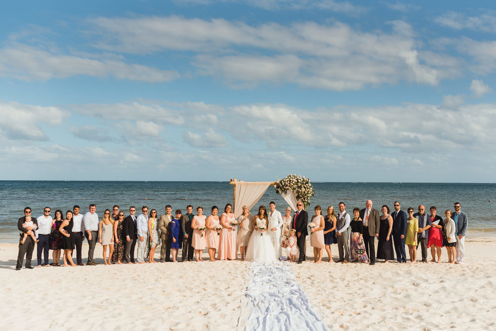 brides and their wedding guests lined up at alter in front of the ocean at Now Sapphire Resort in Mexico