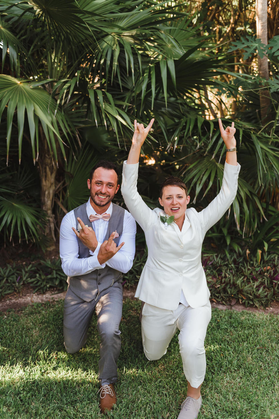 bride and wedding guest crouched down on grass doing rock on symbol with their hands Now Sapphire Resort beach ceremony Mexico