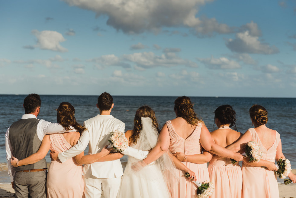 brides and their wedding party facing the ocean with arms around each other on the beach at the Now Sapphire Resort in Mexico how to be really relaxed during your wedding