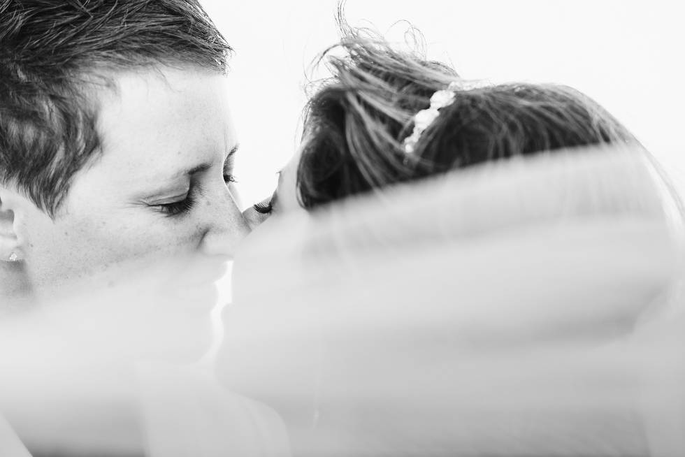 brides kissing on the beach after ceremony at the Now Sapphire Resort in Mexico