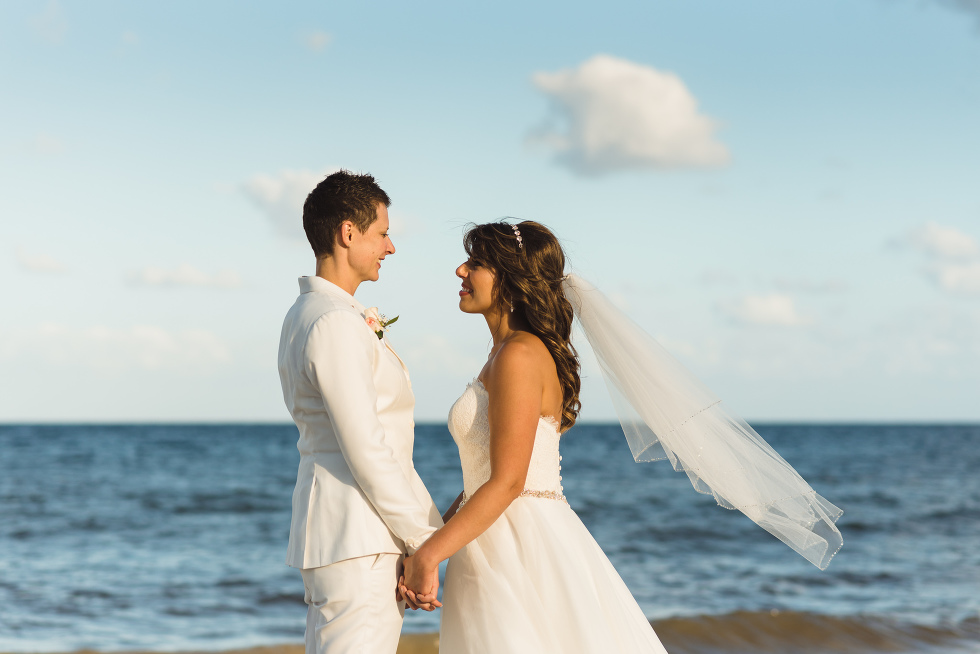 brides facing each other and holding hands in front of the ocean after beach ceremony at Now Sapphire Resort in Mexico