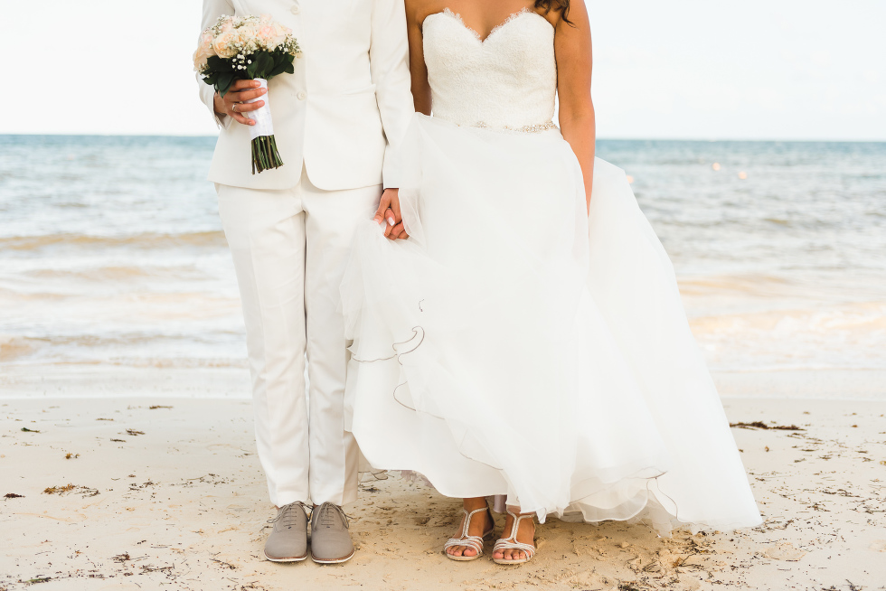 brides standing side by side on the beach holding hands and bouquet after ceremony at Now Sapphire Resort in Mexico