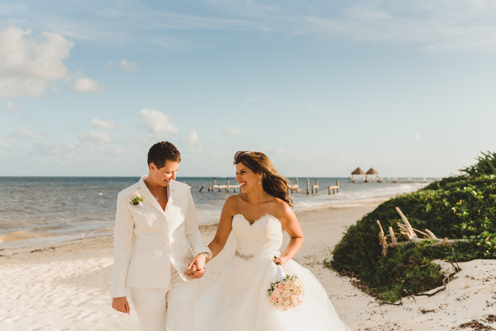 brides walking along beach holding hands after ceremony at Now Sapphire Resort in Mexico