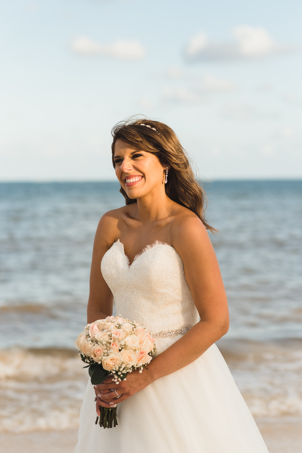 bride smiling and holding bouquet on the beach after ceremony at Now Sapphire Resort in Mexico