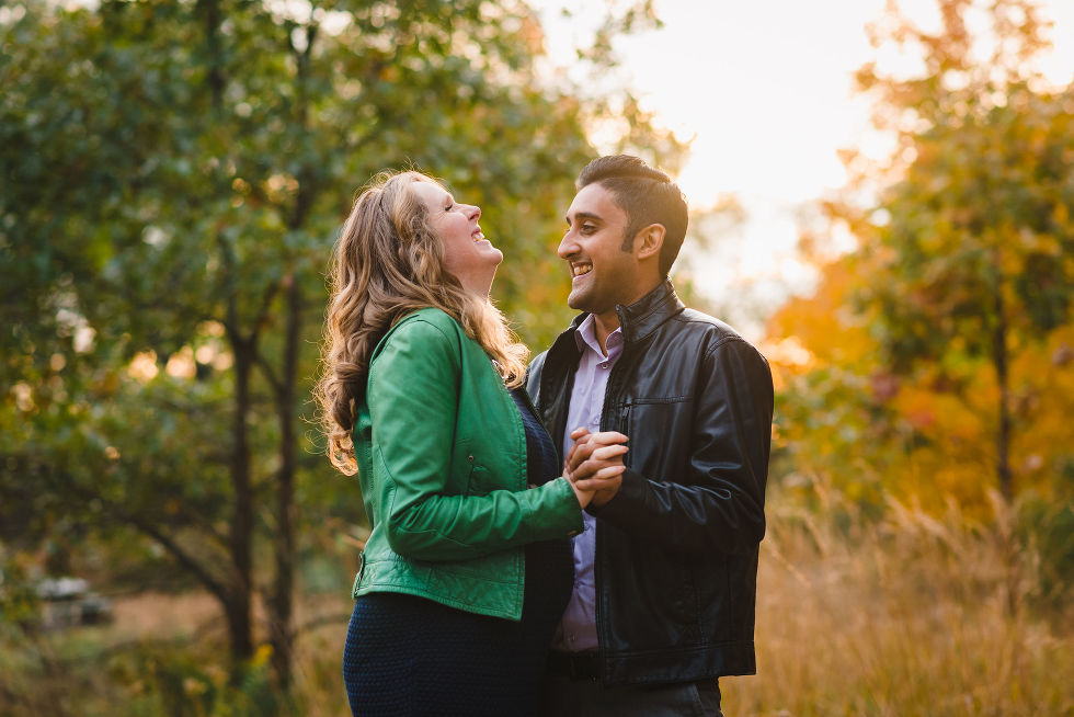 pregnant couple laughing while they slow dance in High Park, Toronto during autumn