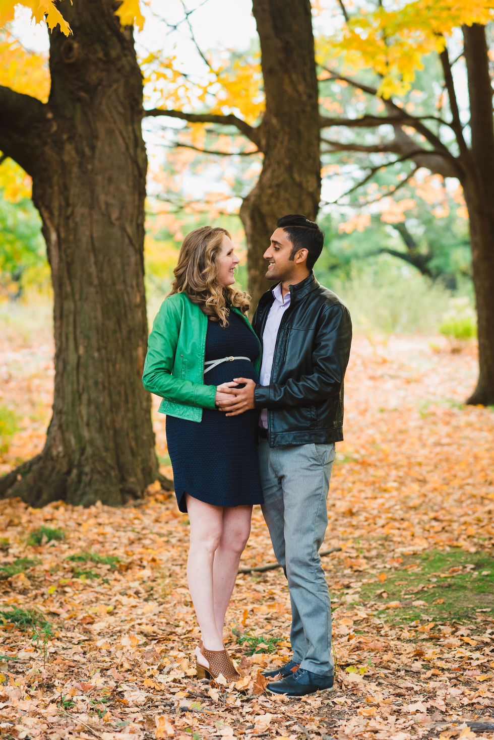 pregnant couple embracing each other under autumn leaves in High Park, Toronto