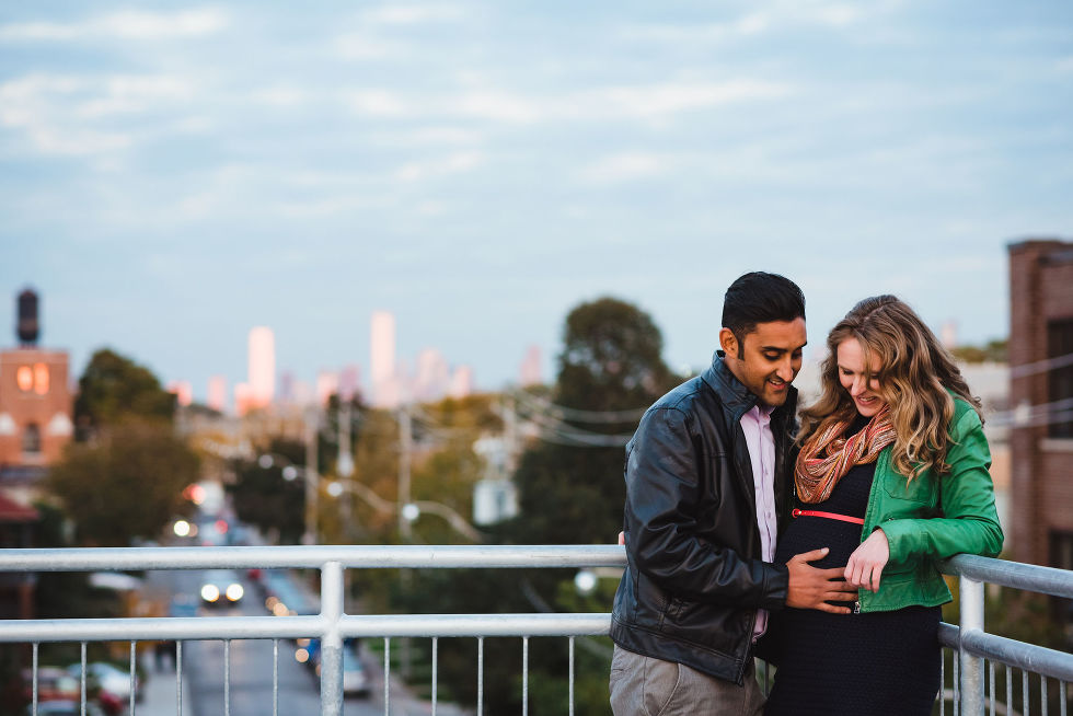 man holding his partners pregnant belly as they stand on platform with Toronto cityscape in background