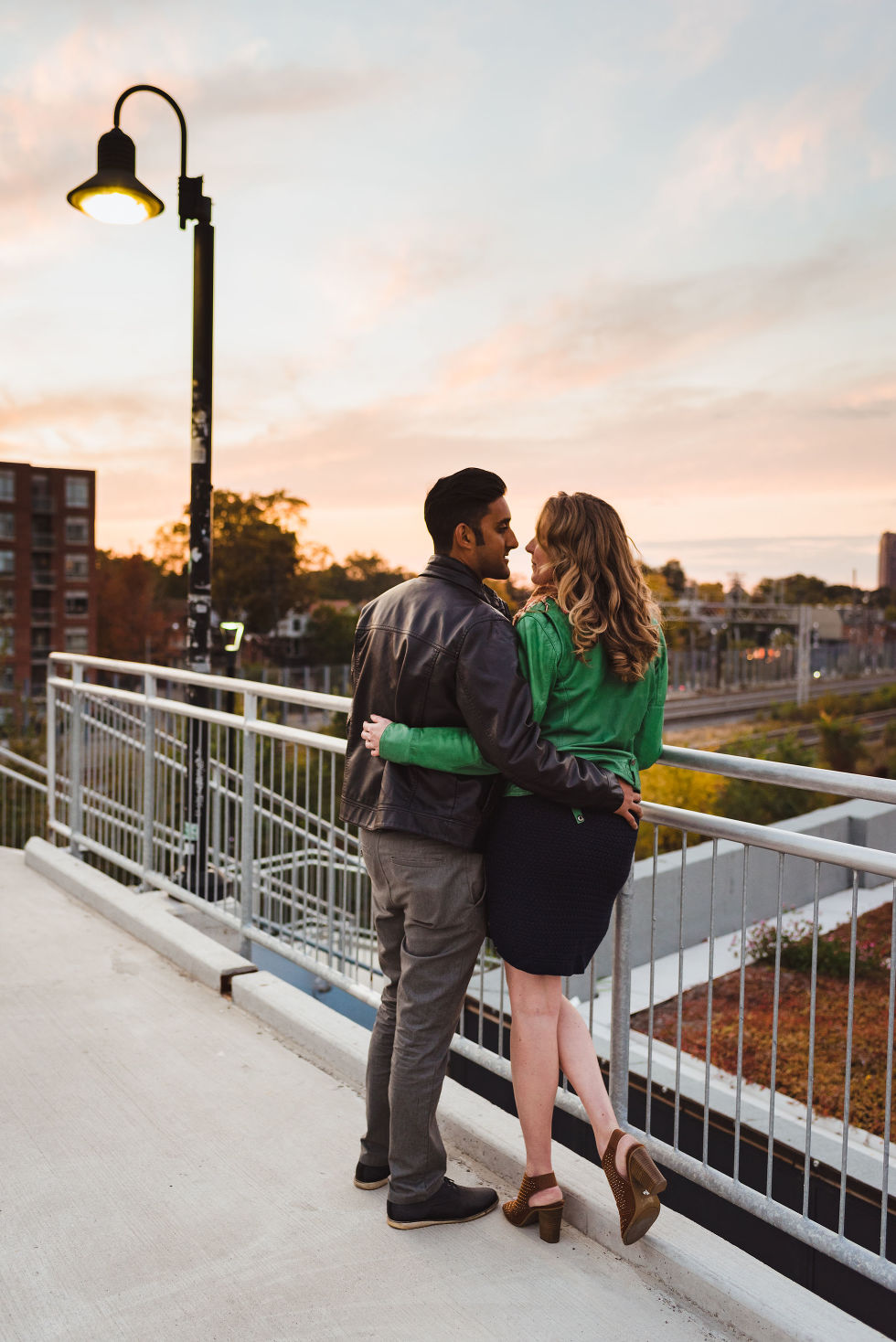man and woman embracing each other on platform overlooking train tracks in the Junction, Toronto