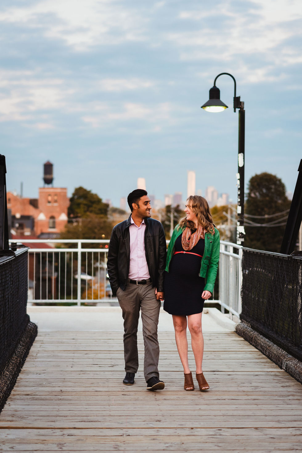 man and woman stroll together holding hands on train platform in the Junction with Toronto skyline in background