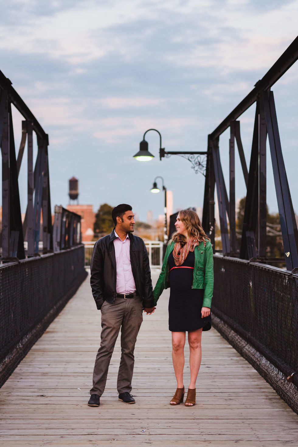 man and woman stroll together holding hands on a bridge in the Junction with Toronto skyline in background
