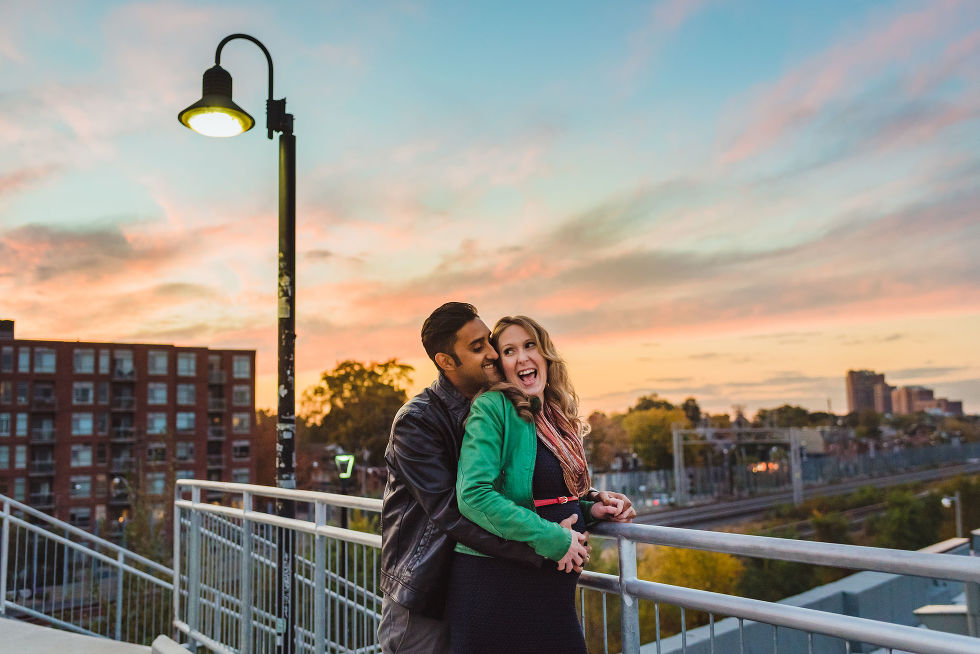 pregnant woman smiling as her partner hugs her from behind on train platform in the Junction, Toronto maternity photos
