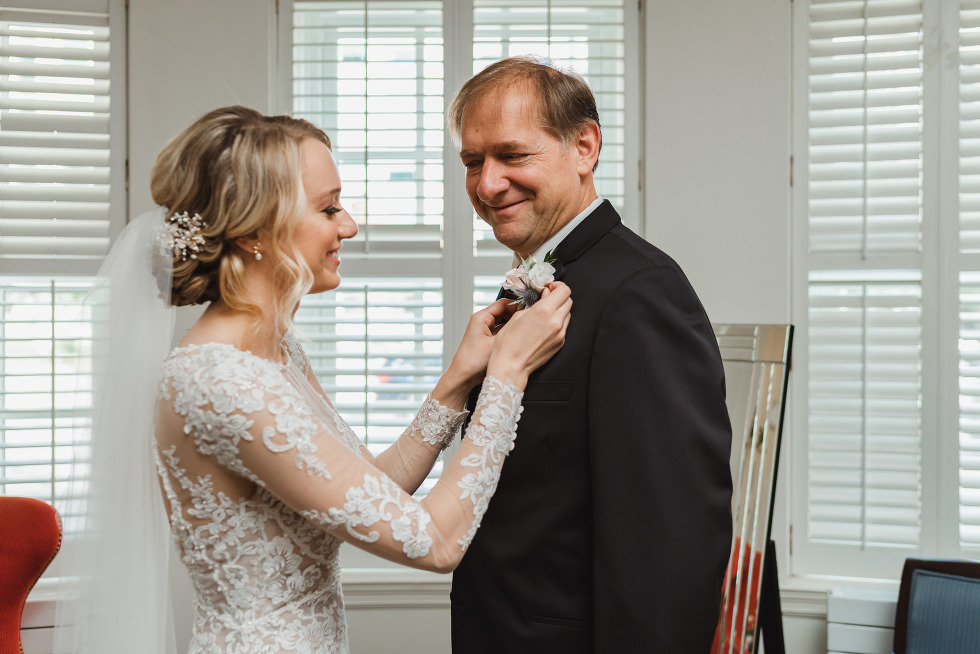 bride pinning boutonniere on her father