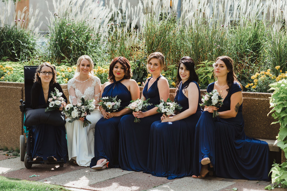 bride sitting with her bridesmaids in front of urban garden, iconic downtown Toronto wedding