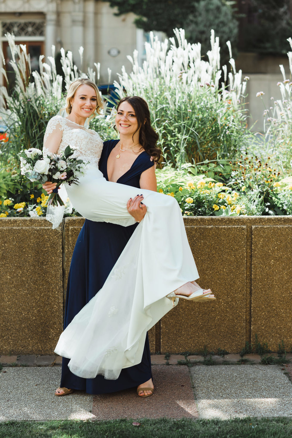 bridesmaid in a blue dress holding bride in her arms in front of an urban garden iconic downtown Toronto wedding
