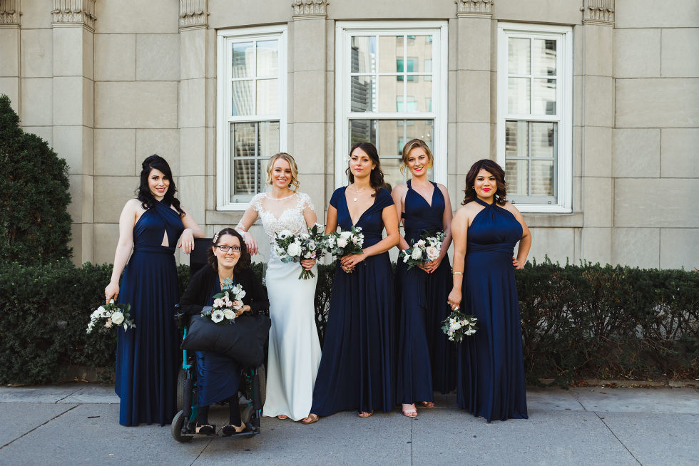 bride surrounded by her bridesmaids and standing in front of an old stone building iconic downtown Toronto wedding