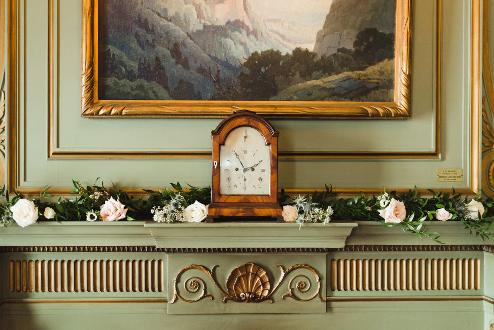 green mantle with flowers, an old brown clock, and a landscape painting iconic downtown Toronto wedding