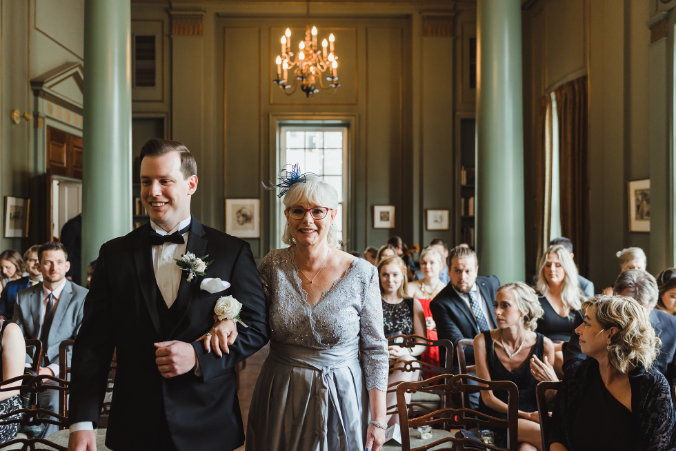 groom entering wedding ceremony with his mother surrounded by wedding guests at the University Club in Toronto, iconic downtown venue