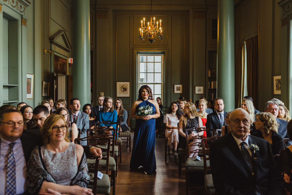 bridesmaid walking down the aisle as wedding guests watch ceremony begin at the University Club iconic downtown Toronto wedding venue