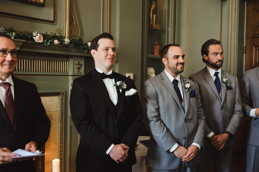 smiling groom standing next to officiant, and groomsmen while wedding ceremony begins at the University Club in Toronto iconic downtown wedding venue