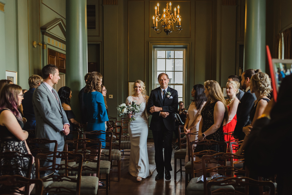 bride being walked down the aisle by her father as wedding guests look on at the University Club in Toronto iconic downtown wedding venue