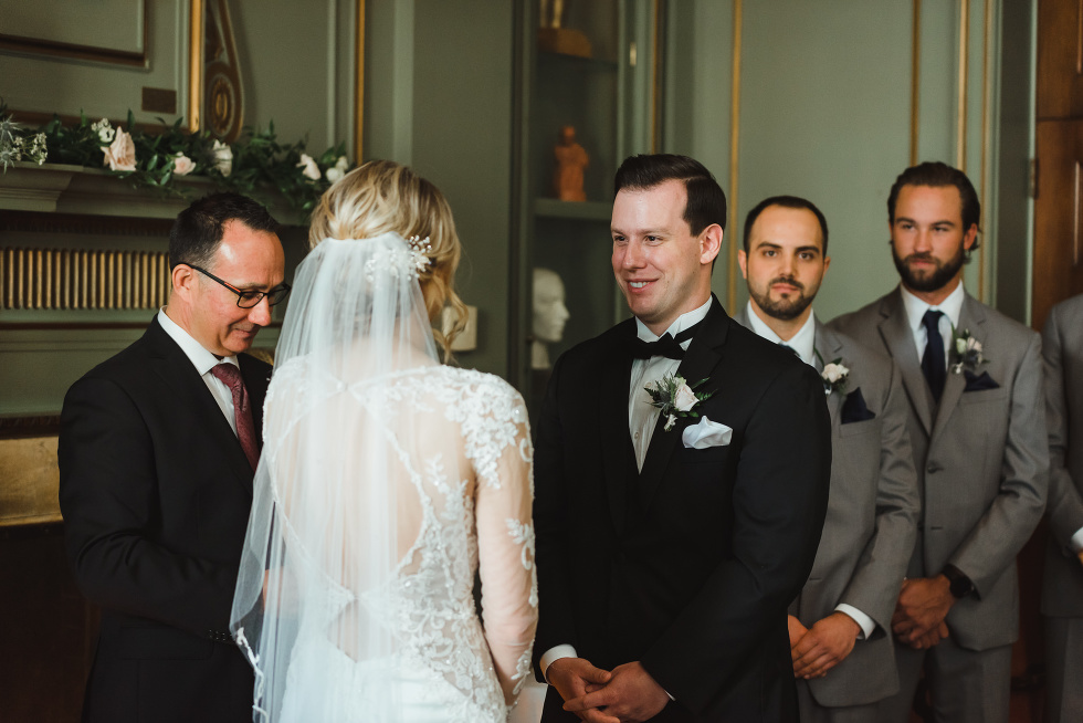 groom smiling at bride during wedding ceremony taking place inside the iconic downtown wedding venue at the University Club in Toronto