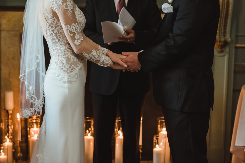 bride and groom holding hands during wedding ceremony taking place inside the iconic downtown wedding venue at the University Club in Toronto