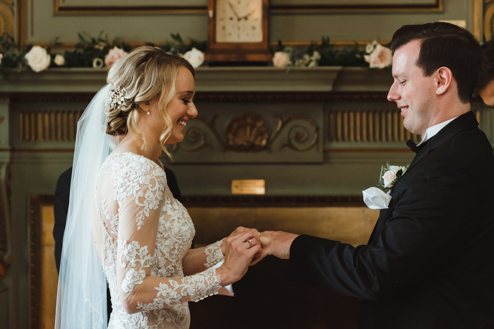bride smiling as she places wedding band on groom