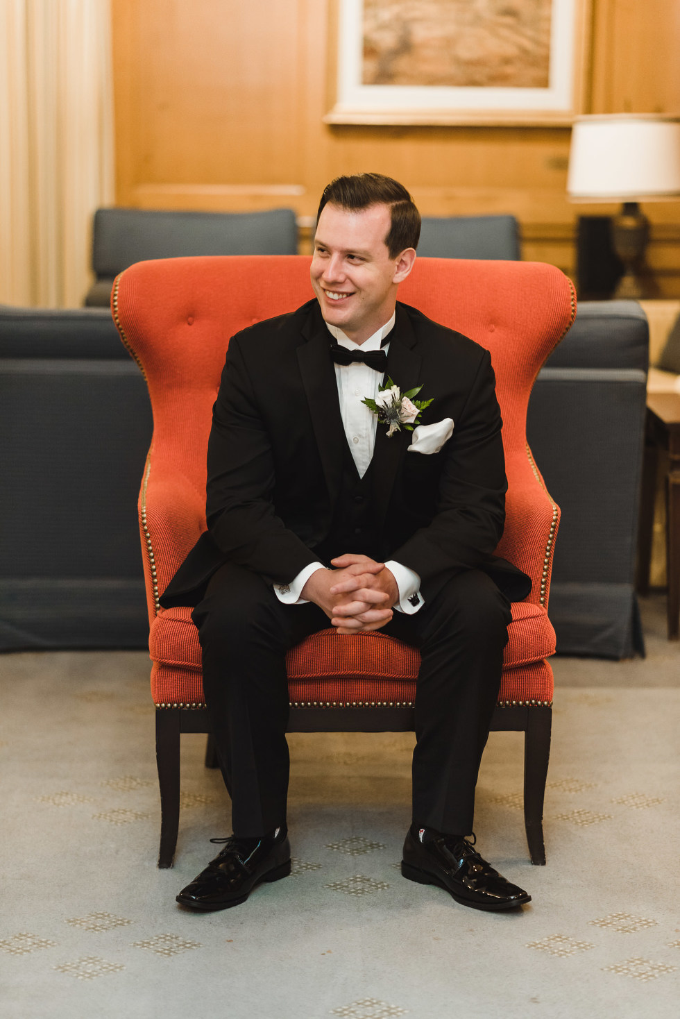 groom sitting in an orange chair before his amazing iconic downtown Toronto wedding