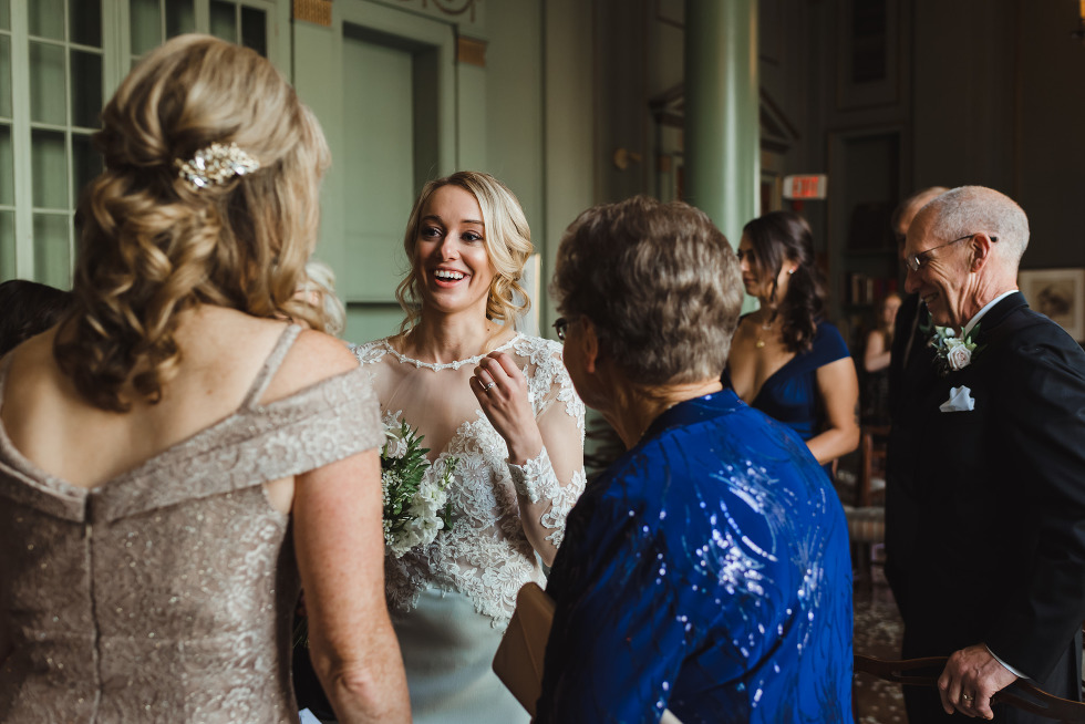 bride smiling as she speaks with wedding guests after her wedding ceremony at the iconic University Club in downtown Toronto
