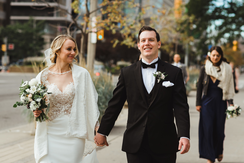 bride and groom smiling and holding hands as they stroll down iconic downtown University Avenue in Toronto