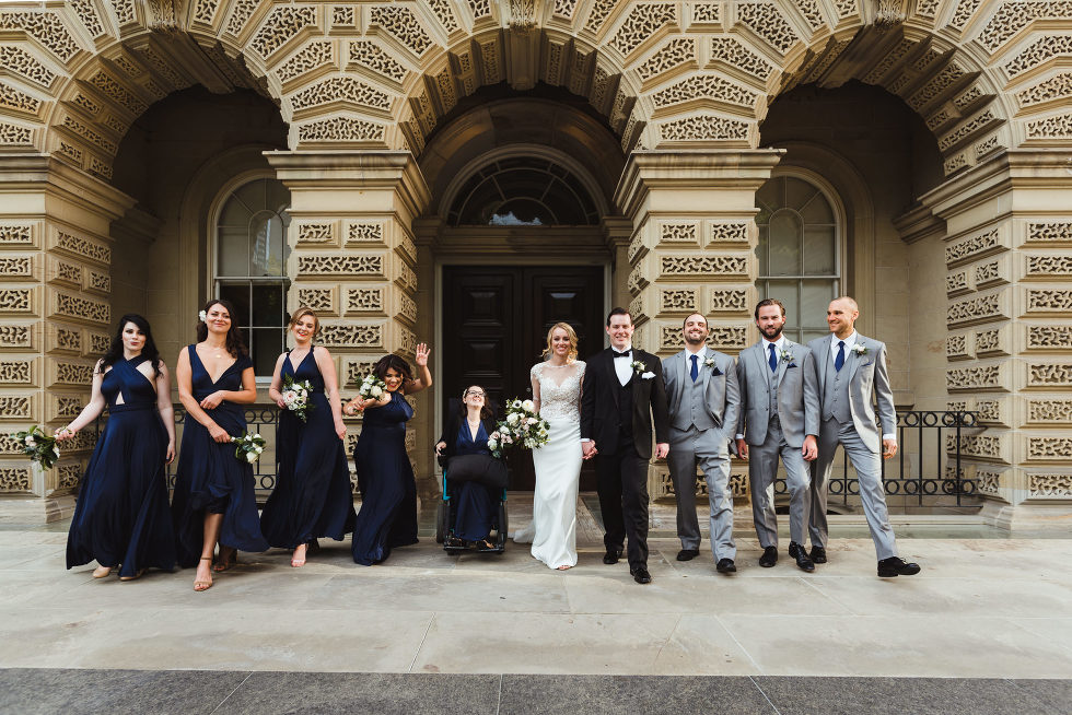 bride and groom standing with their wedding party in front of old and ornate stone arches of a building how to plan an amazing iconic downtown Toronto wedding