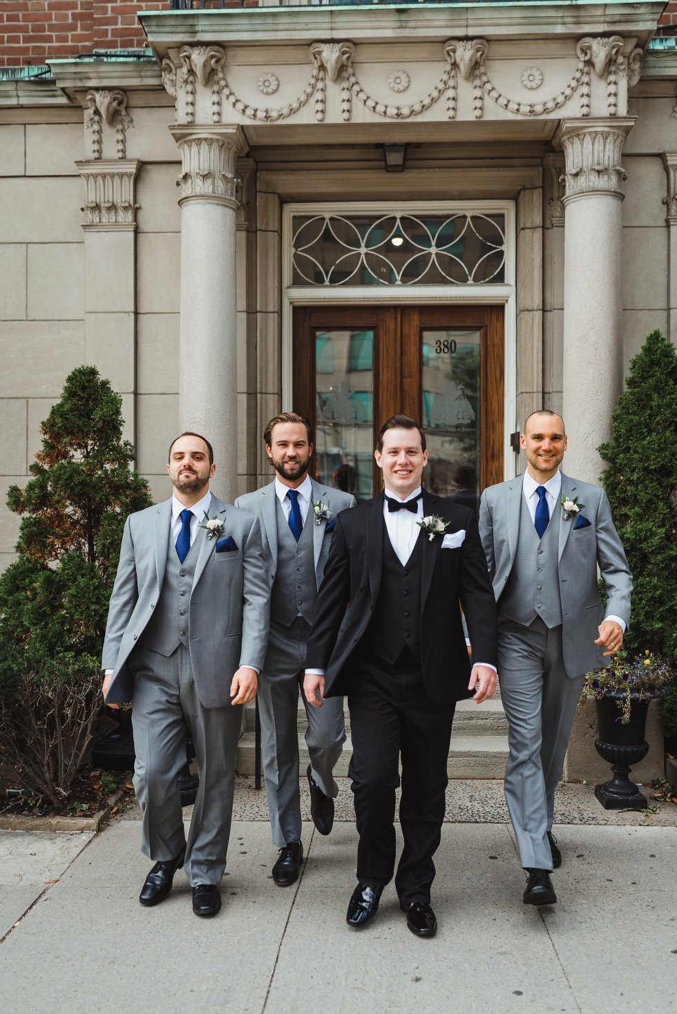 groom in black tuxedo and bowtie walking with his groomsmen in grey suits out of an old building in Toronto before amazing iconic downtown wedding