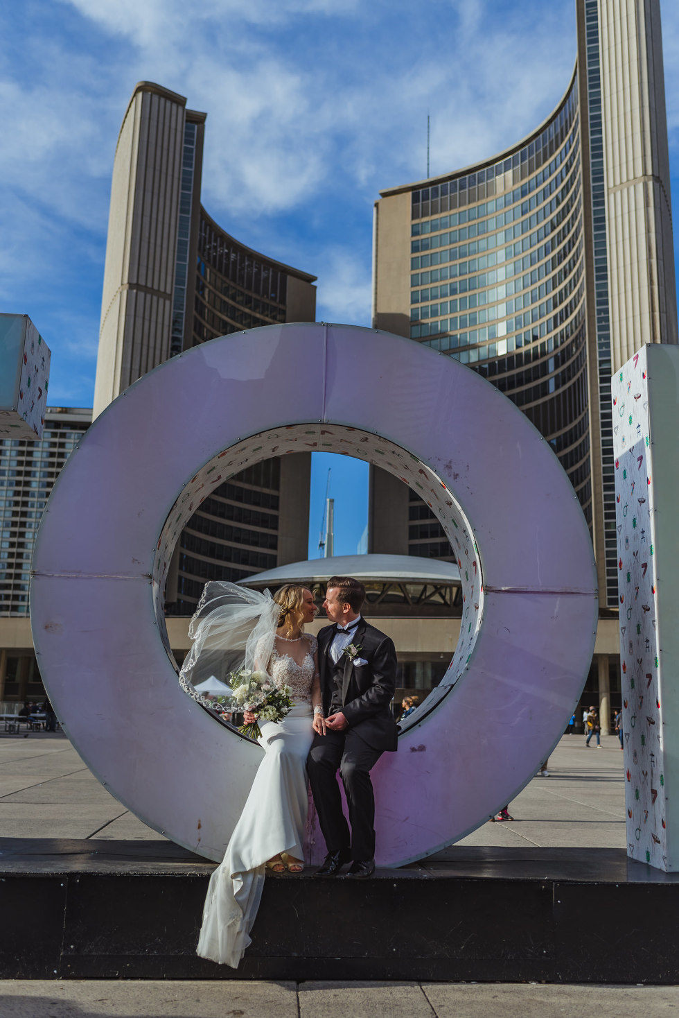 "married couple sitting in the letter ""O"" in Toronto sign at Nathan Phillips Square how to plan an amazing iconic downtown Toronto wedding"