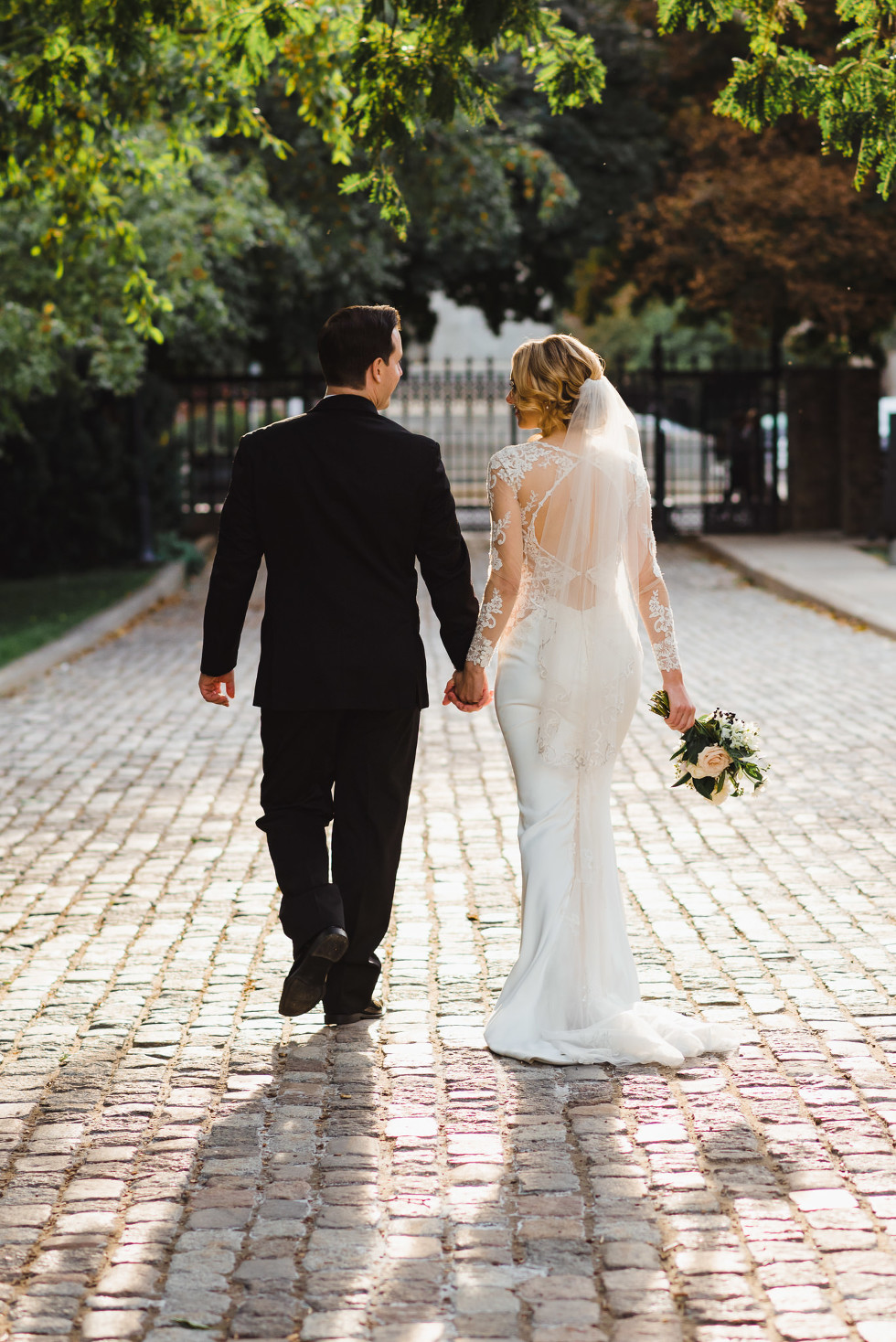 bride and groom stroll hand in hand along a brick pathway in an iconic downtown Toronto wedding