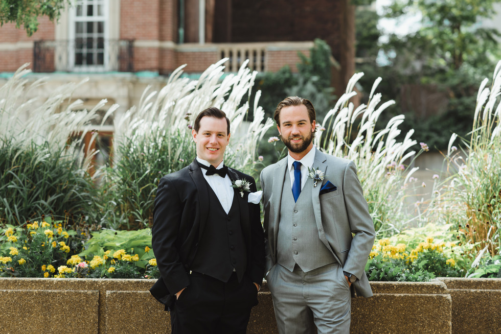 groom in black tuxedo and bowtie standing with a groomsmen in grey suit in front of a garden before amazing iconic downtown Toronto wedding