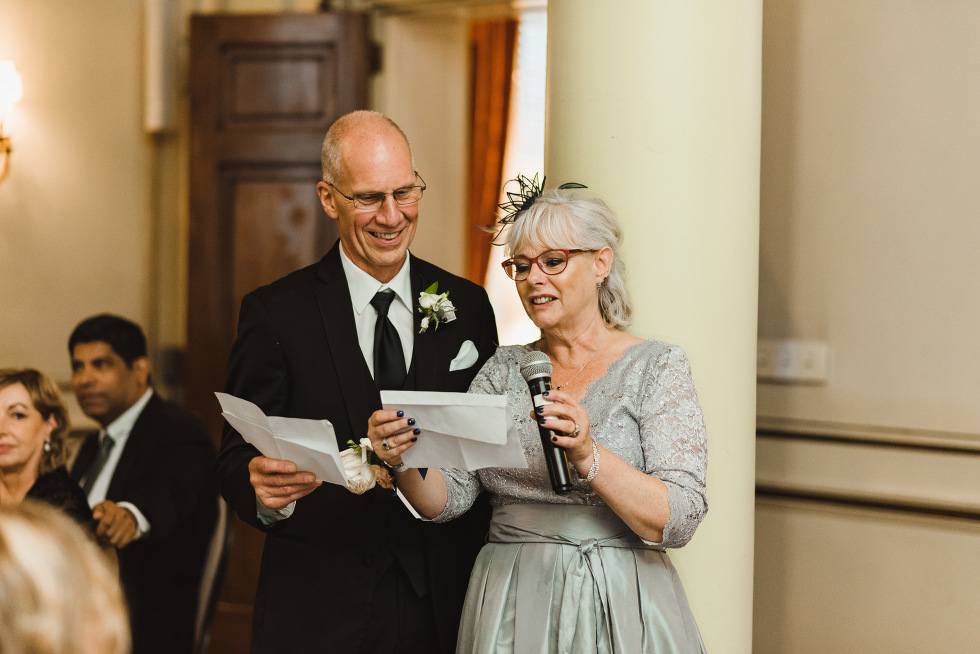 parents of the groom reading wedding speech during reception at the iconic downtown venue of the University Club in Toronto