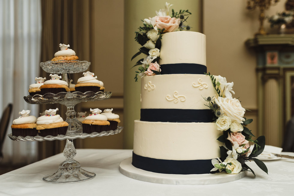 black and white wedding cake with flowers and cupcakes on a three-tiered serving tray University Club wedding downtown Toronto
