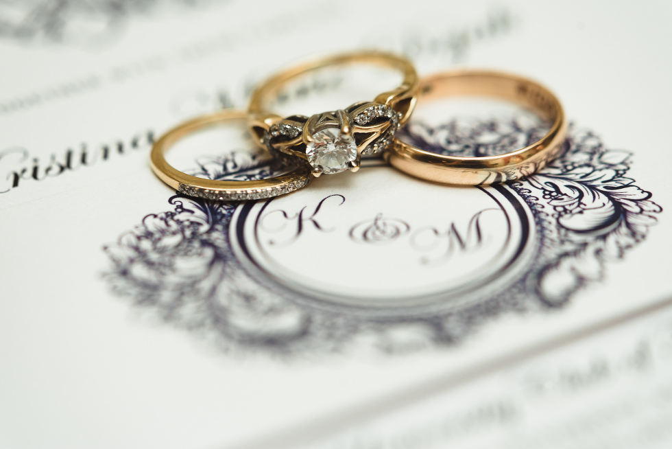 bride and grooms wedding rings place over a wedding card at the iconic University Club downtown Toronto wedding venue
