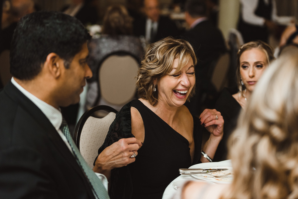 wedding guest laughing at her table with other guests during reception at the iconic University Club downtown Toronto wedding venue