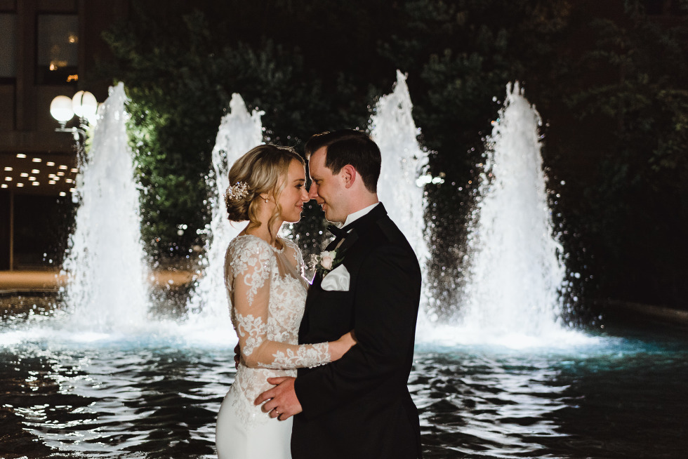 bride and groom in a tight embrace in front of a water fountain with 4 columns of water shooting upwards behind them iconic downtown Toronto wedding photographer Gillian Foster